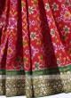 Red and green patola work saree
