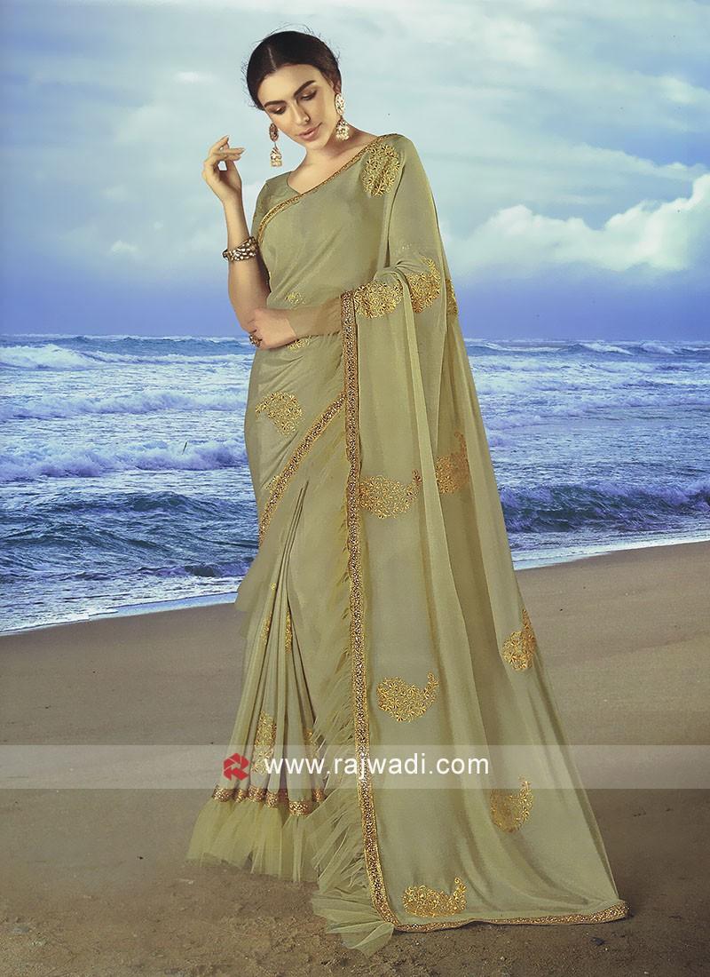 Beige chiffon saree with matching blouse.