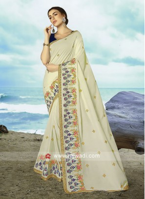 Cream art silk saree with dark blue blouse.