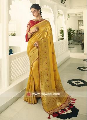 Golden yellow saree with beautiful red zari work design blouse piece.
