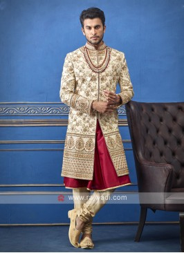 groom cream and red sherwani