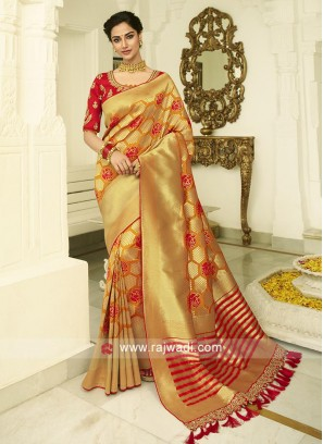 Mustard yellow banasari silk saree with red unstiched blouse.
