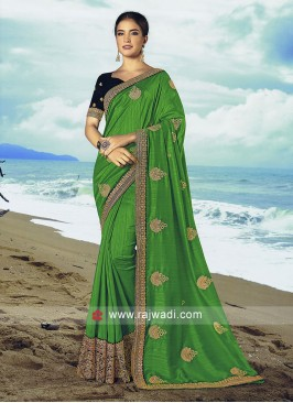 Parrot green art silk saree with dark blue blouse.