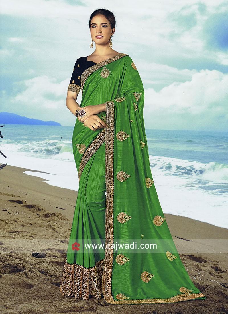 Parrot green art silk saree with dark blue blouse.