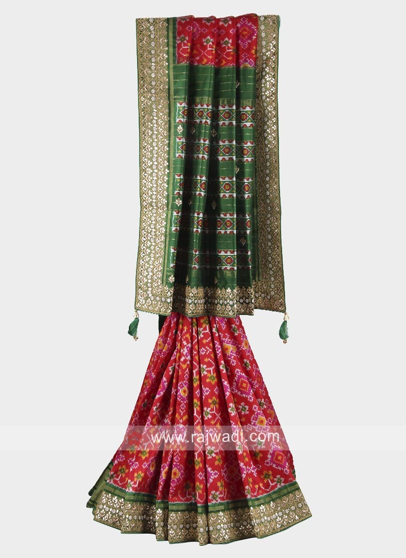 Red and green patola work saree