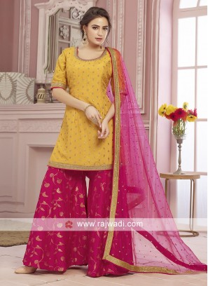 Yellow and rani color chiffon gharara suit.